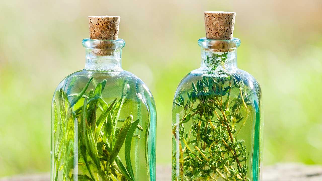 Kräuteressig in Flaschen mit Rosmarin und Thymian