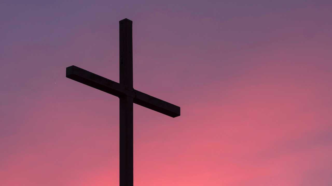 Kreuz vor rötlichem Himmel als Symbol für Karfreitag und das Sterben von Jesus