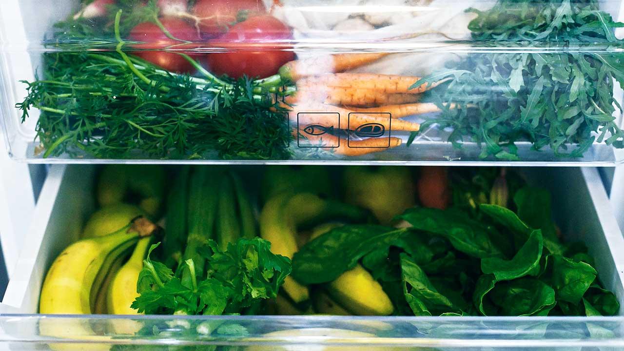Früchte, Gemüse und Salat in einem offenen Kühlschrank