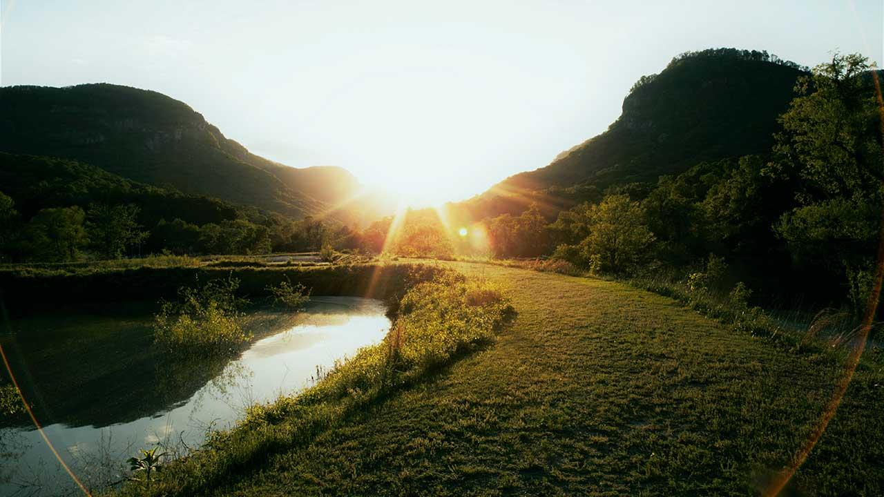 Landschaft mit Weiher und Hügeln, erhellt von Sonnenlicht