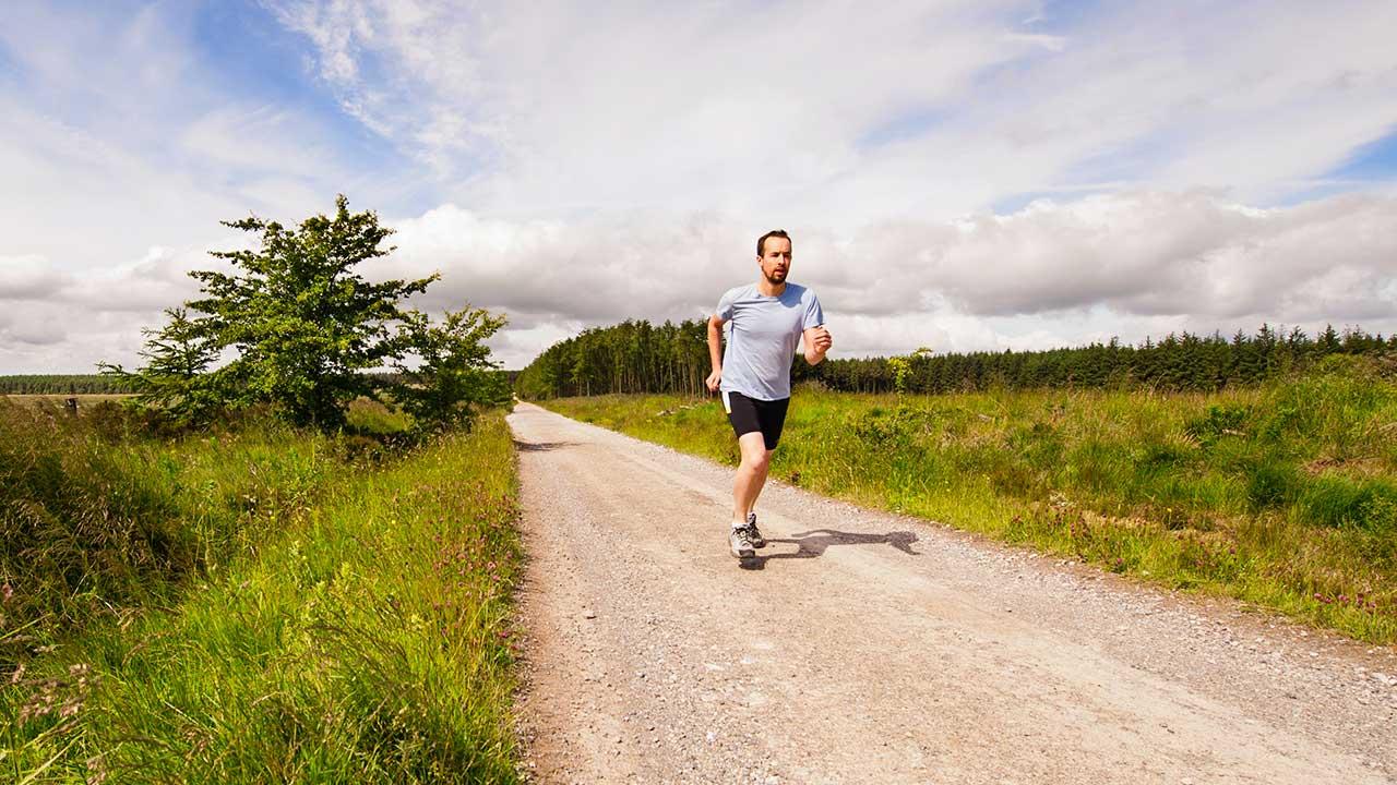Mann rennt eine Landstrasse entlang