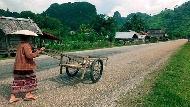 Frau mit Schubkarren in einem laotischen Dorf