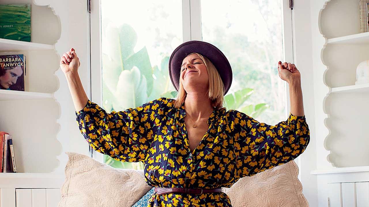 Frau sitzt in einer Wohnung und ist gelöst und entspannt