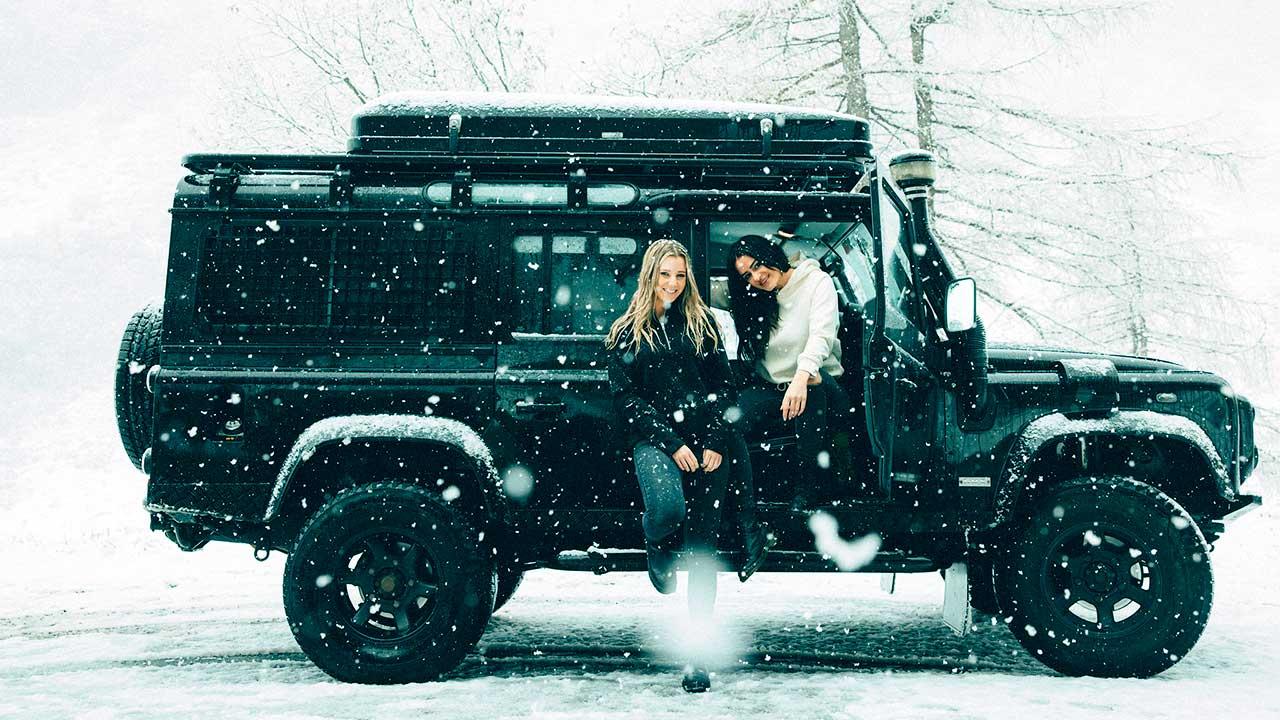 Zwei junge Frauen sitzen in einem Jeep und es schneit