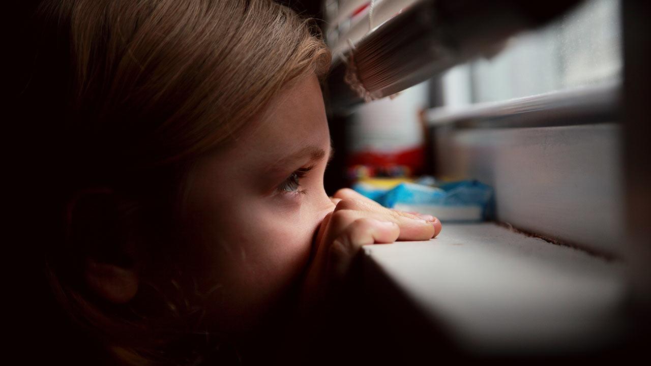 Ein Mädchen lugt durch den Vorhang | (c) unsplash