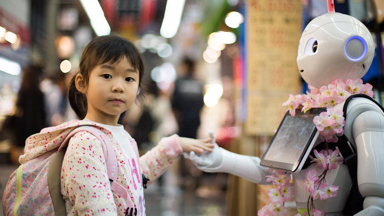 Asiatisches Mädchen gibt Roboter die Hand | (c) unsplash