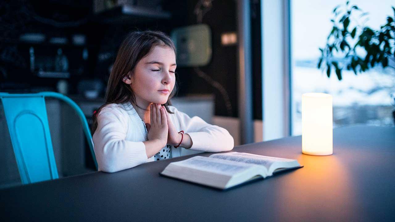 Mädchen sitzt an einem Tisch und betet über einer offenen Bibel