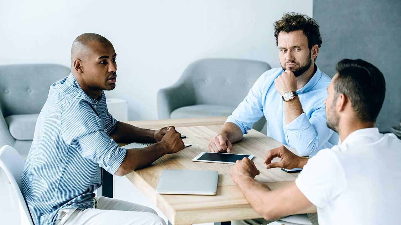 Drei Bürokollegen diskutieren zusammen an einem Tisch