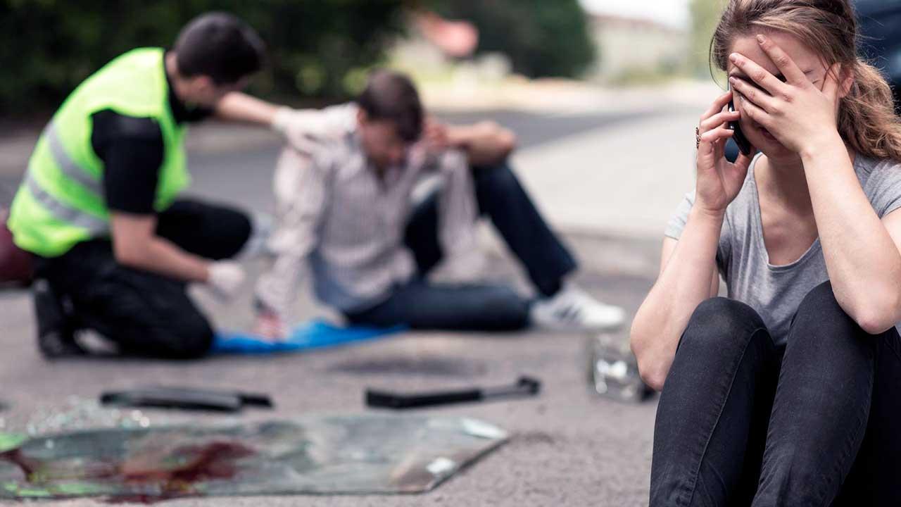 Unfallstelle, im Vordergrund eine verzweifelte, sitzende Frau
