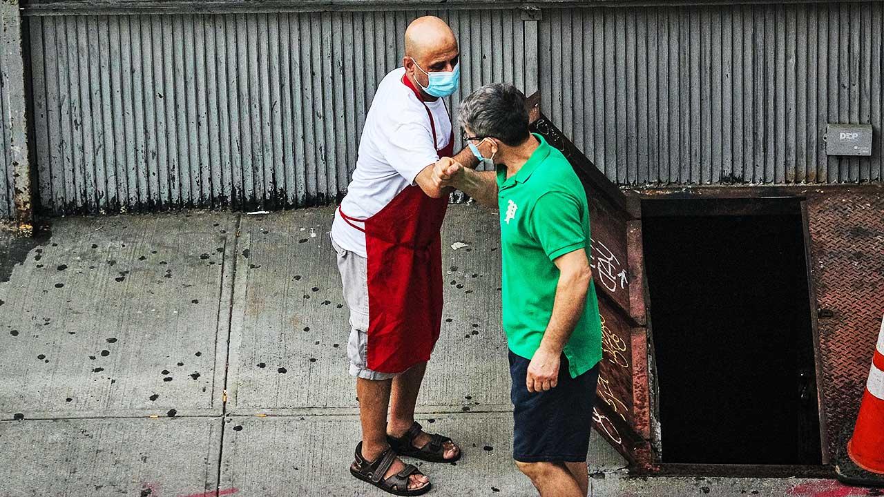 Zwei Männer mit Schutzmasken begrüssenn sich per Arm