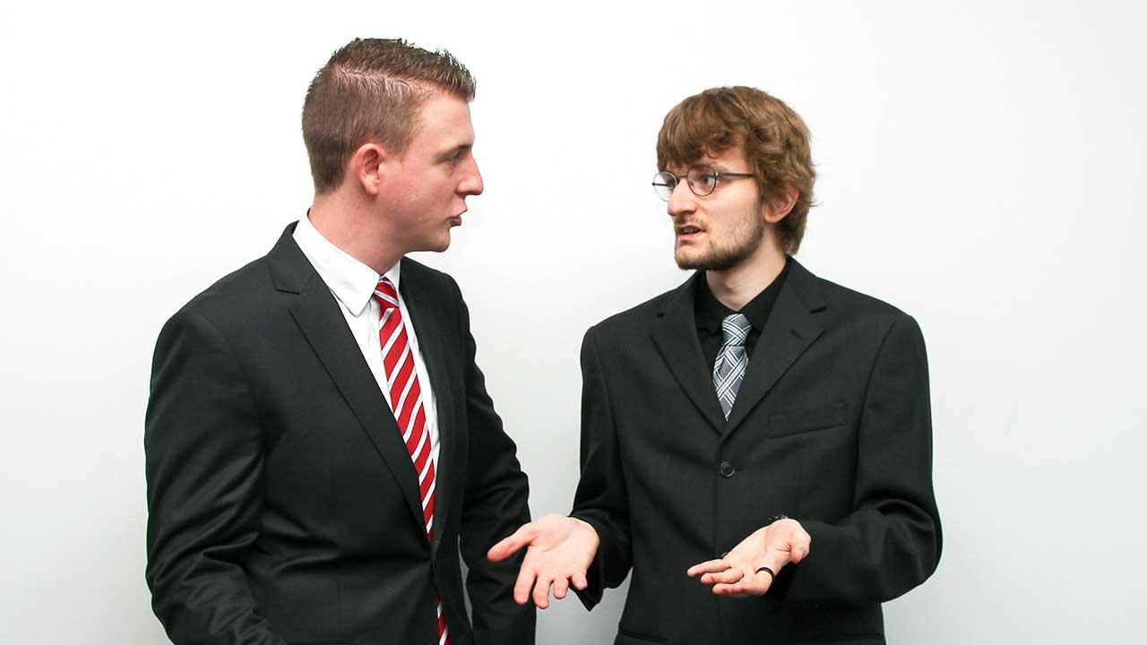 Zwei junge Männer in Anzügen in einer ernsten Diskussion