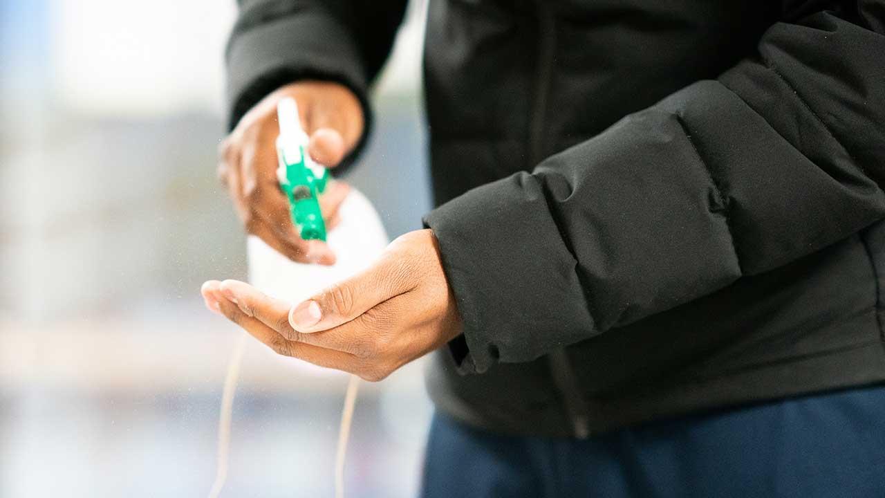 Männerhände benutzen ein Desinfektionsmittel