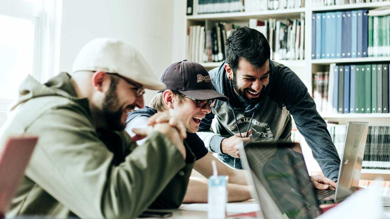 Drei Männer haben Spass und Freude bei der Zusammenarbeit