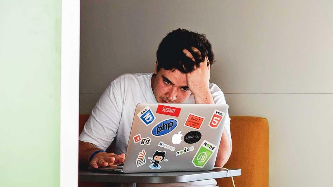 Mann arbeitet konzentriert und vielleicht bereits gestresst an einem Coworking-Arbeitsplatz