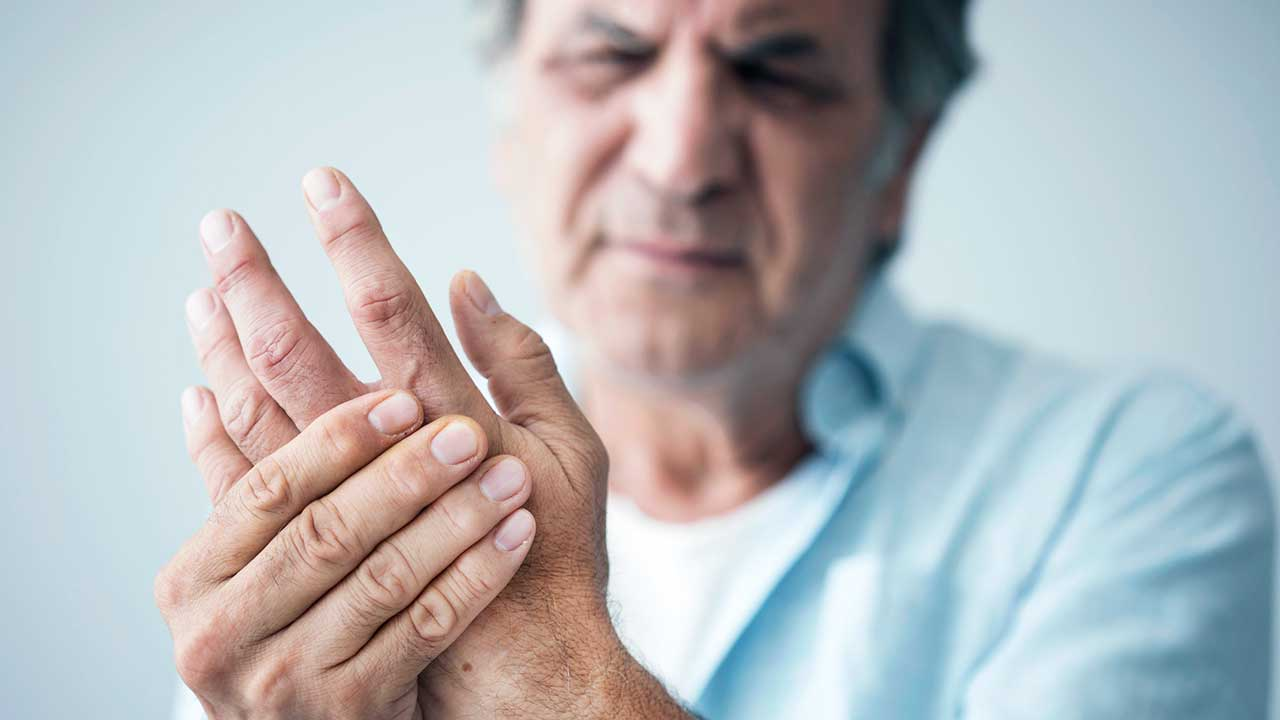 Mann hält Hände, weil seine Finger schmerzen