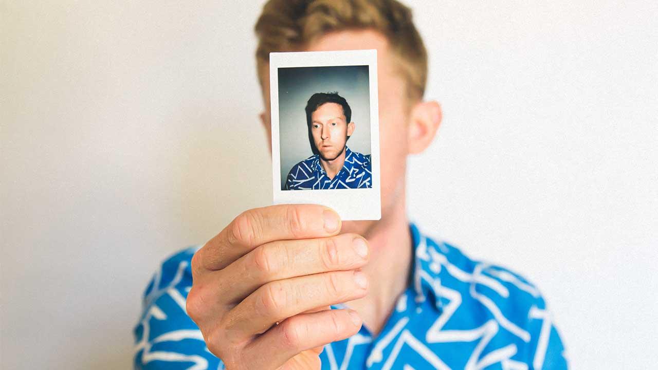 Mann hält Polaroid-Foto von sich vor sein Gesicht