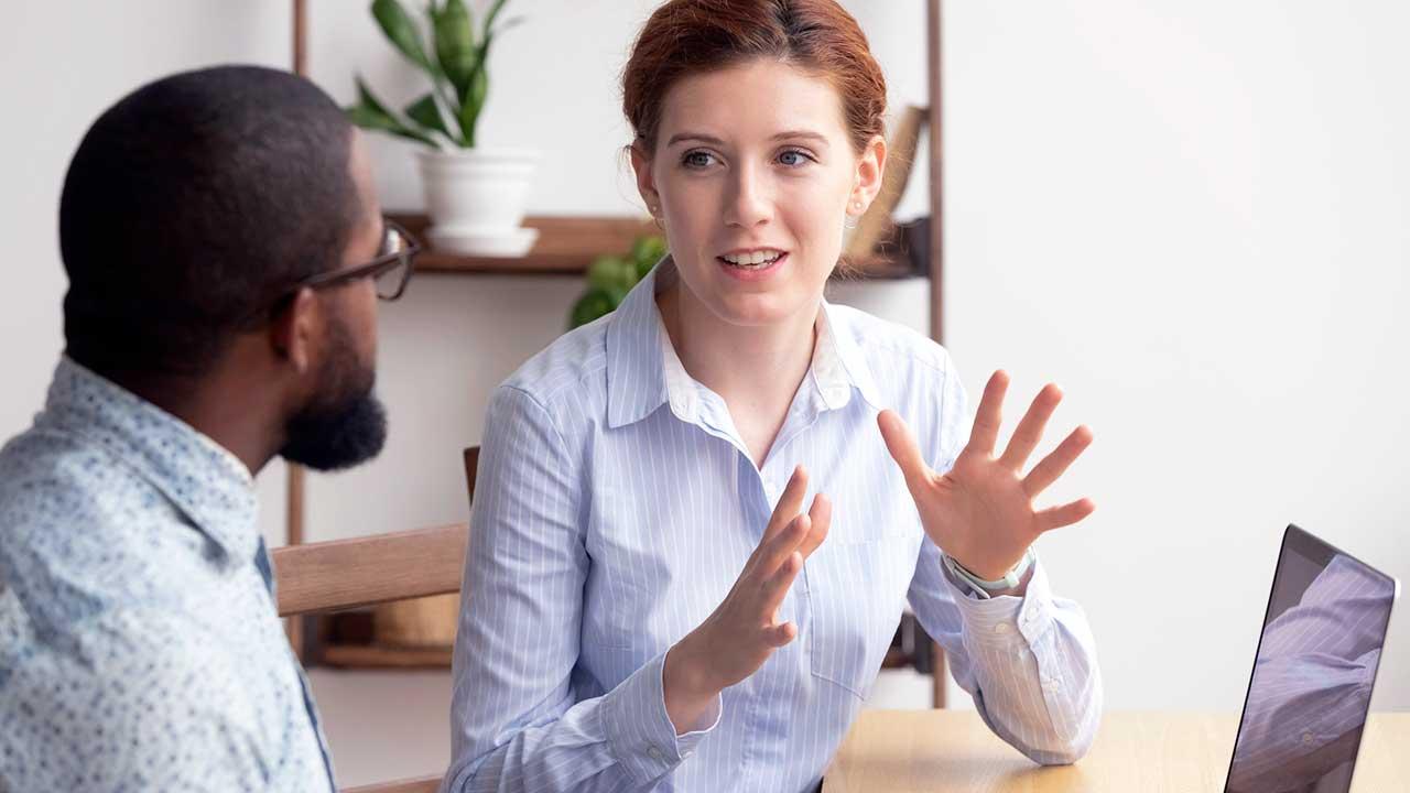 Frau spricht mit einem Bürokollegen