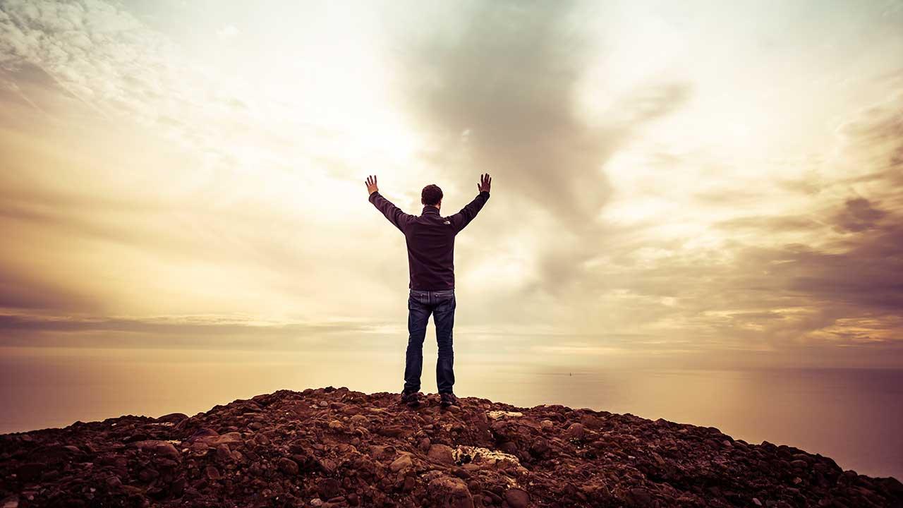 Mann steht an der Küste und erhebt seine Arme in den Himmel | (c) Guillaume de Germain/Unsplash