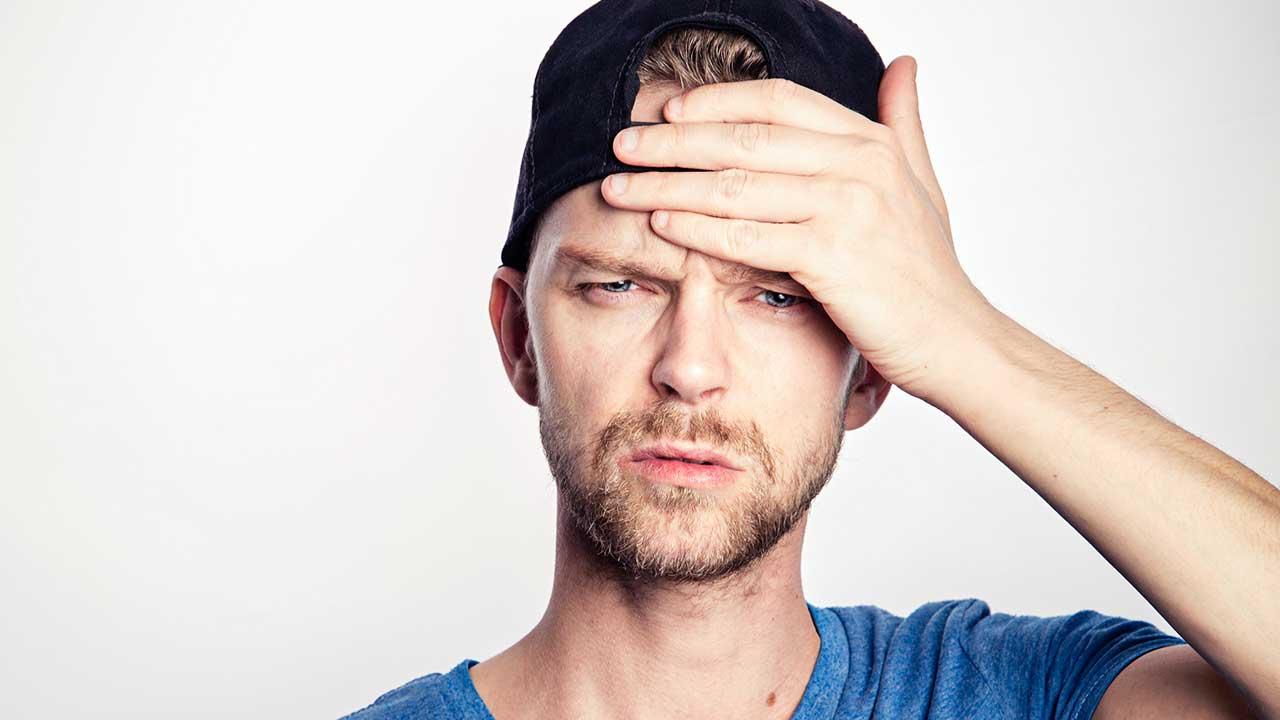 Mann hält Hand an Stirn als Zeichen von Kopfweh oder Vergesslichkeit