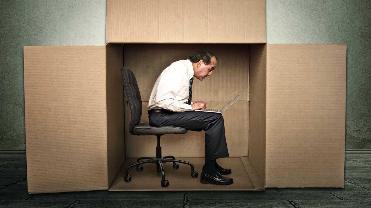 Mann arbeitet mit seinem Laptop in einer grossen, aber engen Kartonschachtel