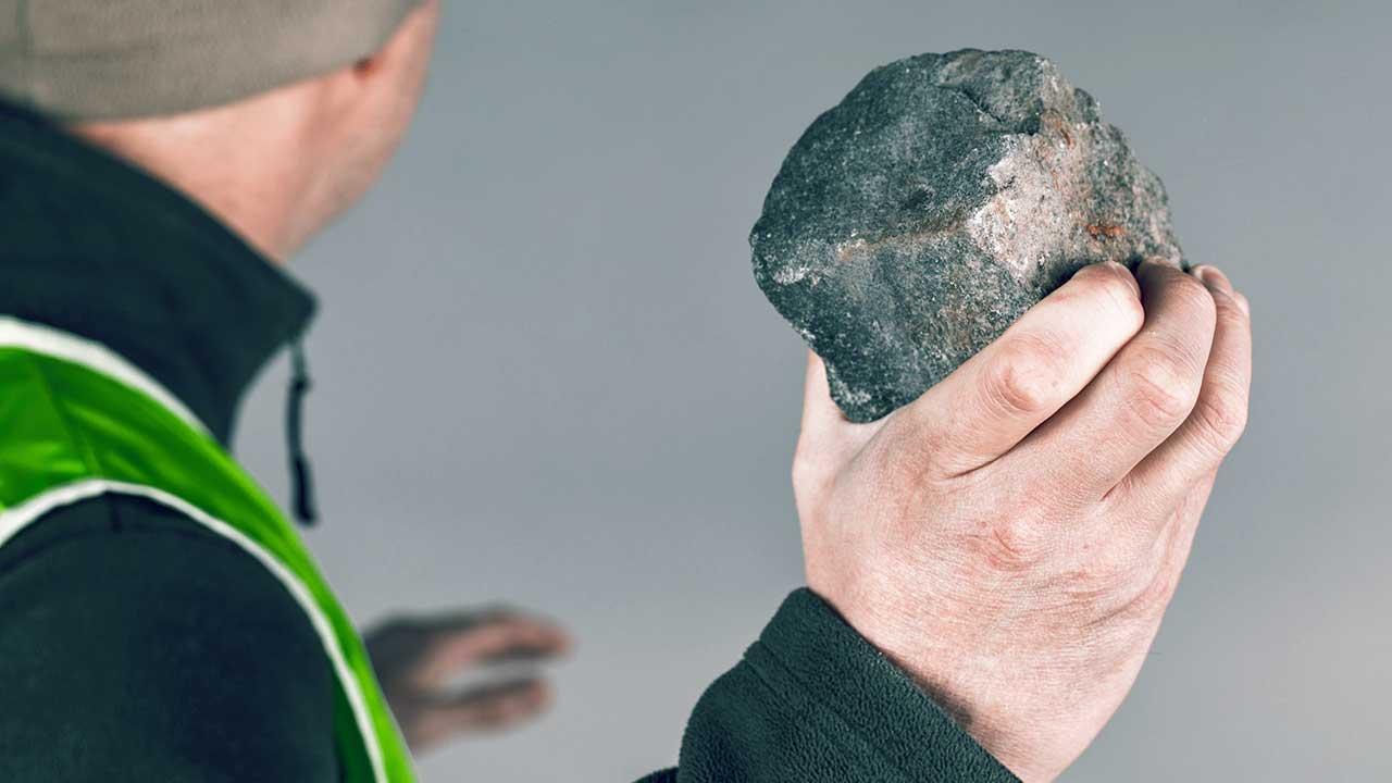 Rückansicht auf einen Mann, der einen Stein in der Hand hält