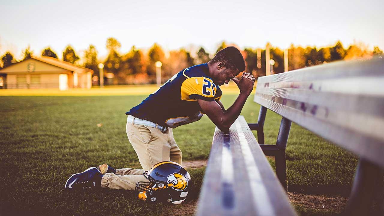 Rugby-Spieler kniet vor einer Sitzbank und betet konzentriert
