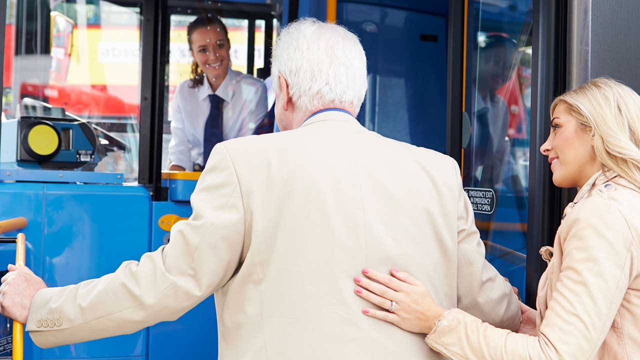 Frau hilft einem älteren Mann in den Bus