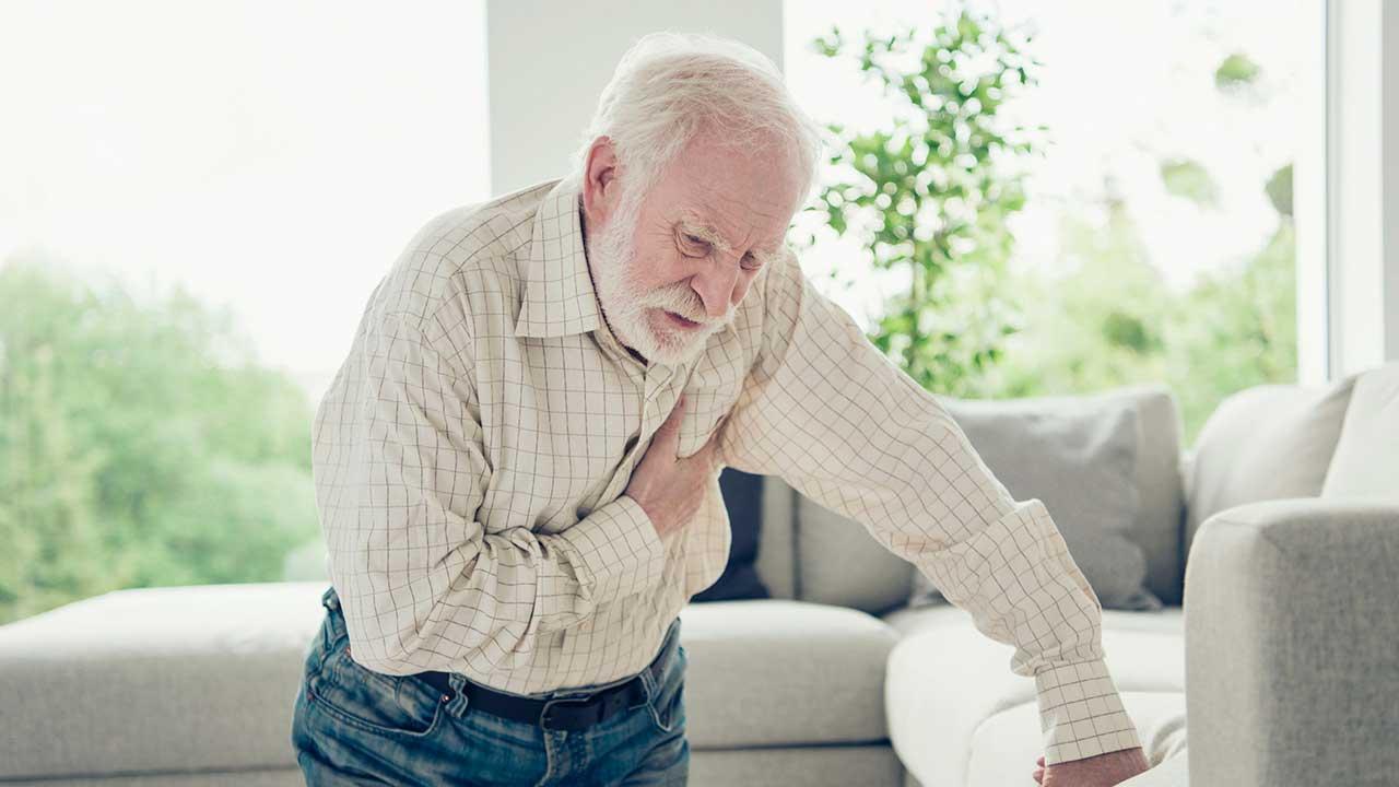 Mann hält wegen Herzinfarkt Hand auf Brust