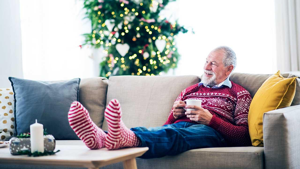 Mann sitzt zufrieden auf dem Sofa, im Hintergrund ein Weihnachtsbaum