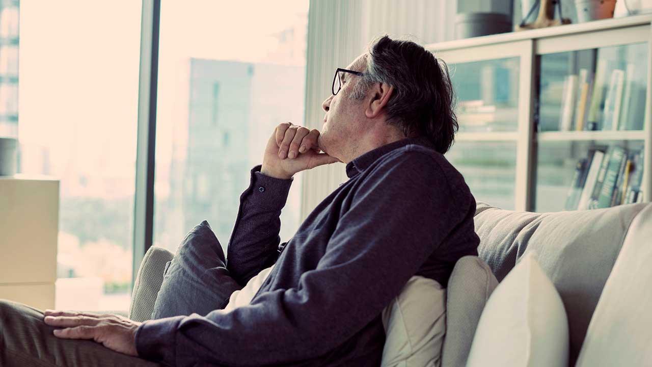 Mann sitzt auf Sofa und denkt in Ruhe nach