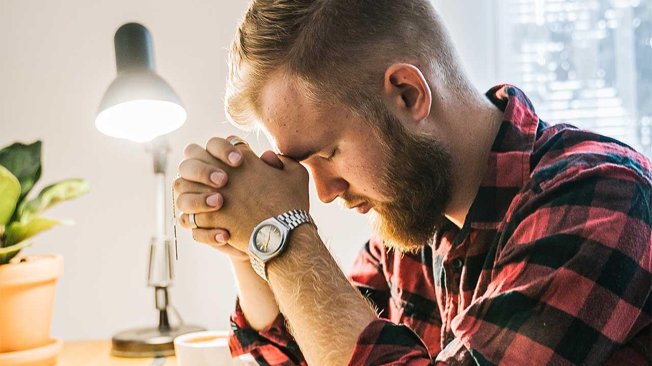 Mann sitzt an einem Tisch und betet konzentriert