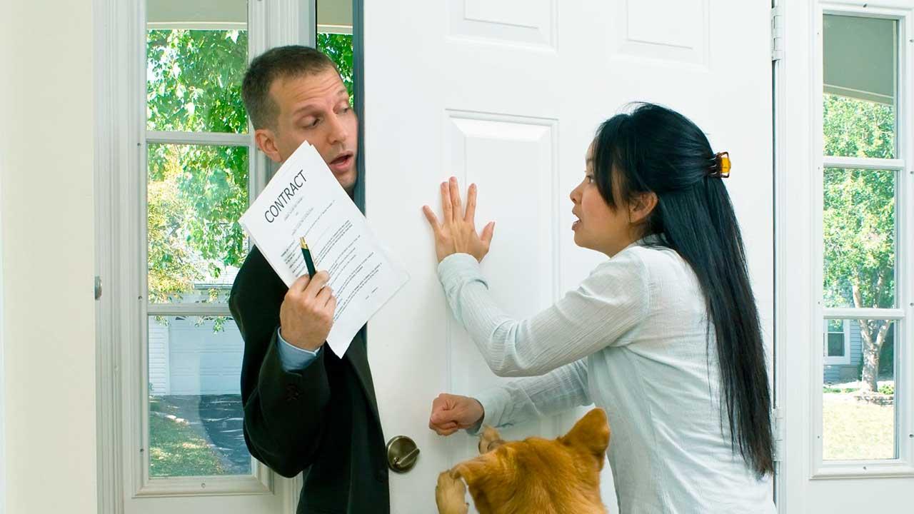 Frau drückt Türe zu, um aufdringlichen Verkäufer loszuwerden