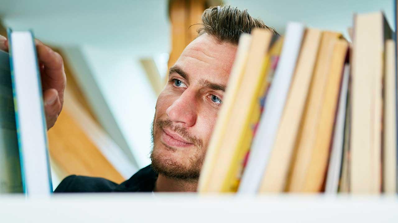 Mann sucht iin einem Regal einer Bibliothek nach einem Buch