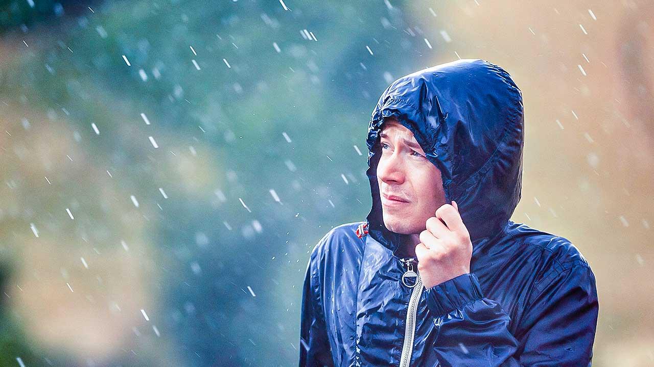 Mann in einer Regenjacke wird leicht verregnet