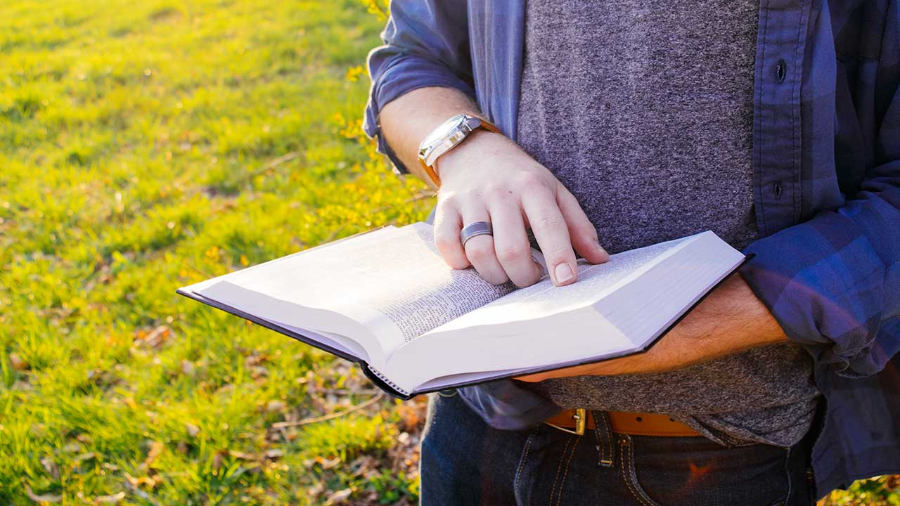 Mann hält offen Bibel und liest mit Finger darin