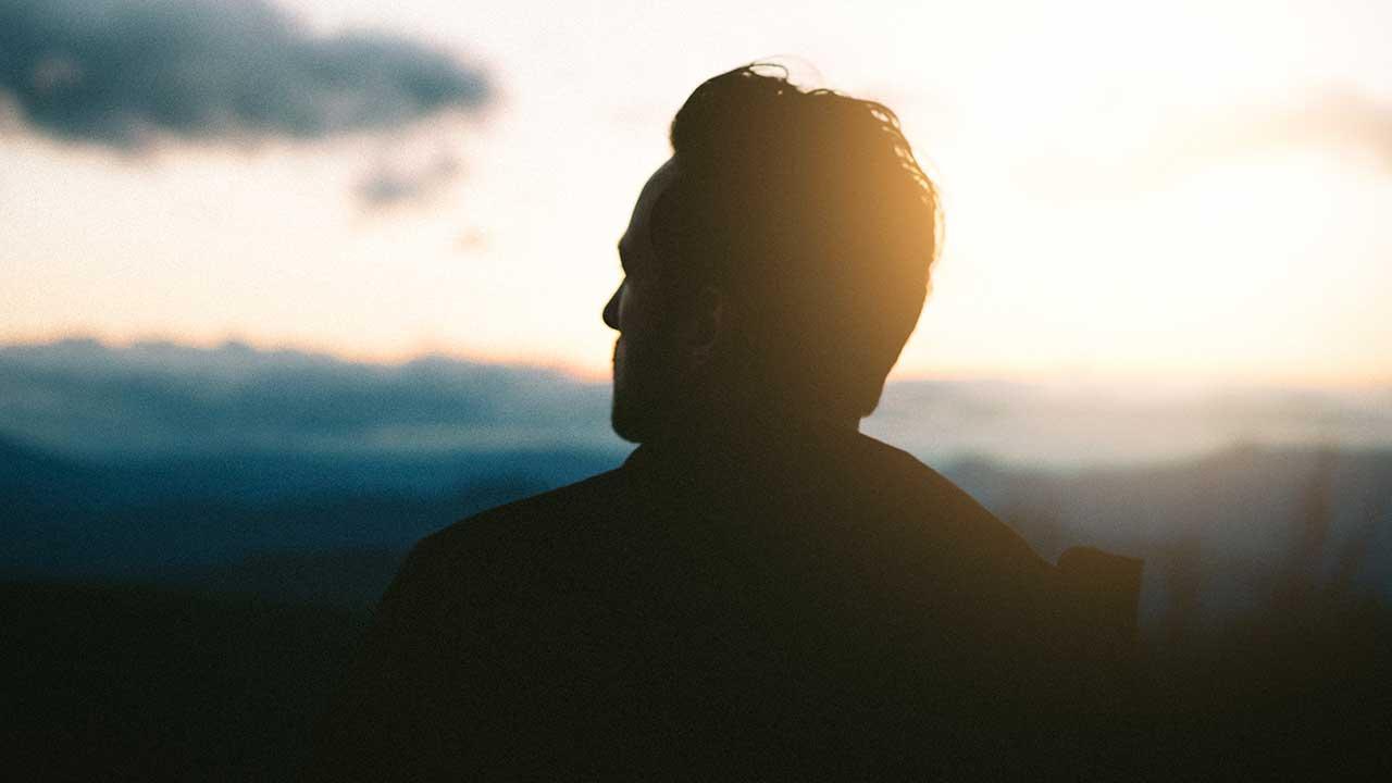 Mann als dunkle Silhouette wird seitlich von Sonnenlicht angeleuchtet