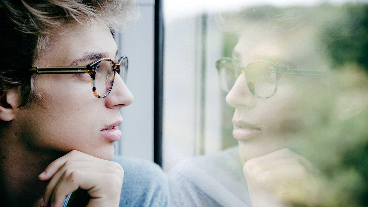 Mann blickt in Fenster und wird dort reflektiert