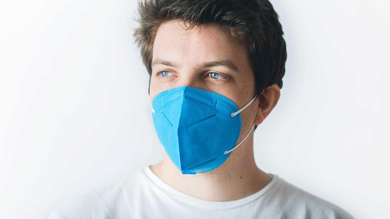 Junger Mann trägt eine blaue FFP2-Maske