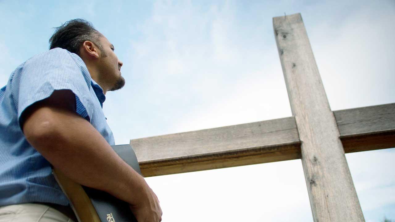 Mann mit Bibel im Arm blickt zum Kreuz hoch