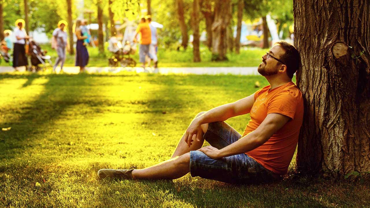 Mann sitzt angelehnt an einen Baum und entspannt sich