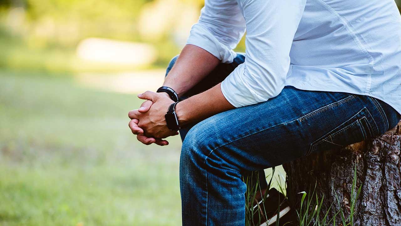Mann sitzt auf einem Baumstamm und betet