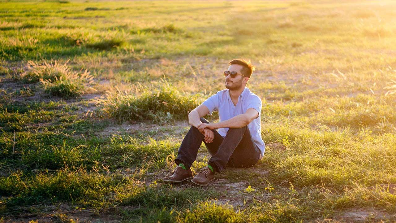 Mann sitzt im Sommer auf Gras und ruht sich aus
