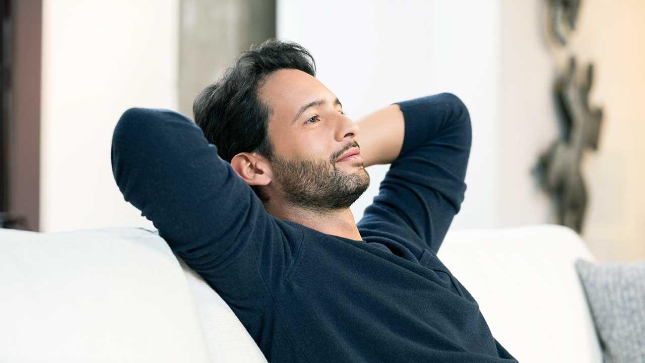 Ein junger Mann sitzt entspannt im Sofa und macht Pause