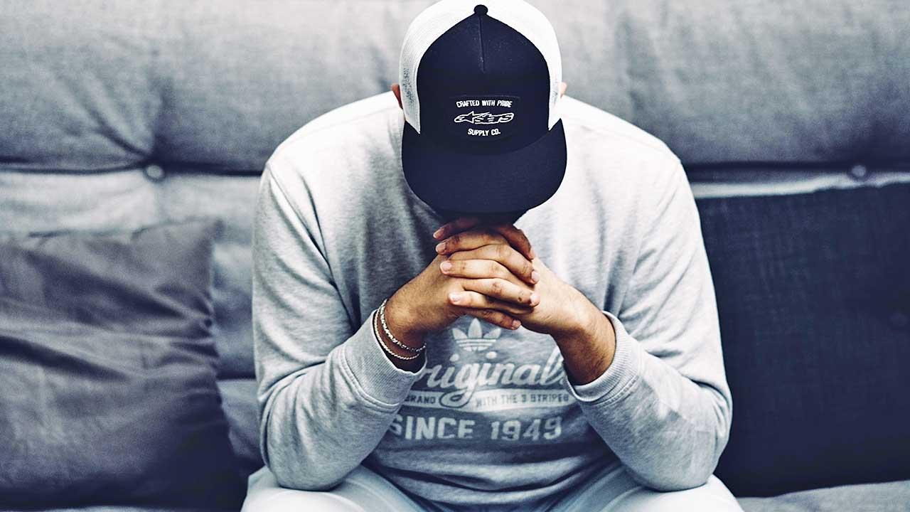 Mann sitzt auf einem Sofa, mit Kopf geneigt, am Beten oder Nachdenken
