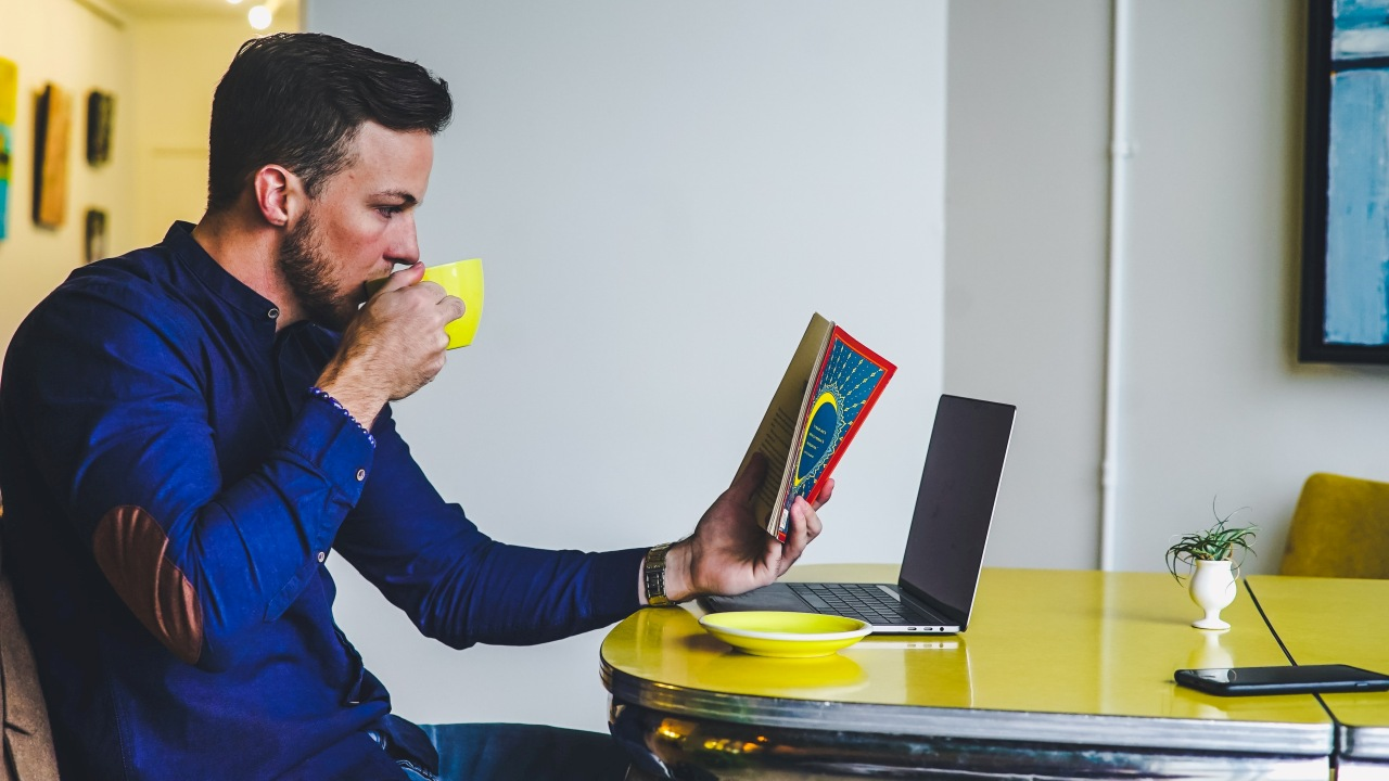 Ein Mann sitzt an einem Tisch und liest ein Buch.