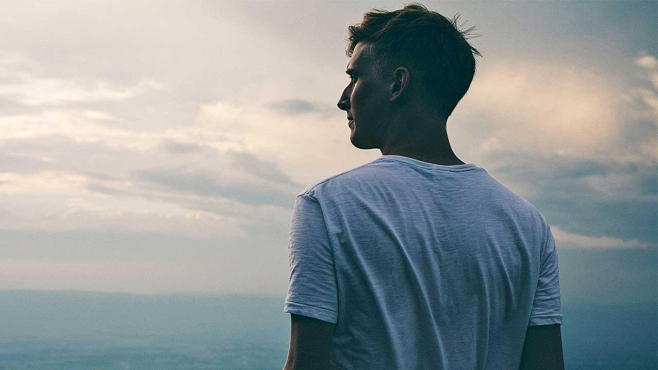 junger Mann blickt über eine weite Landschaft