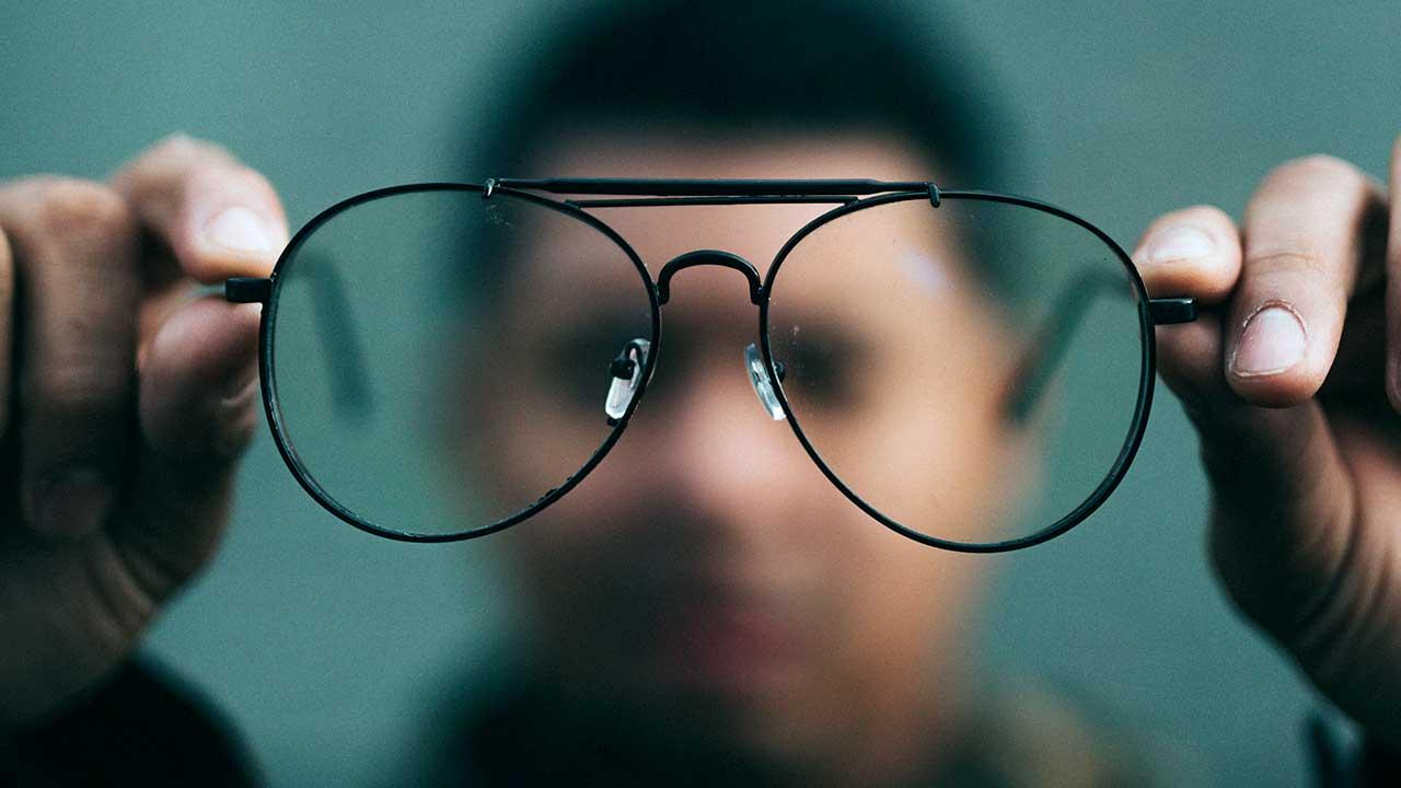 Mann hält Brille vor sich