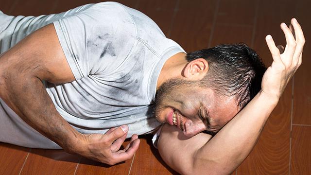 Mann liegt schmerzverzerrt auf dem Boden | (c) unbekannt