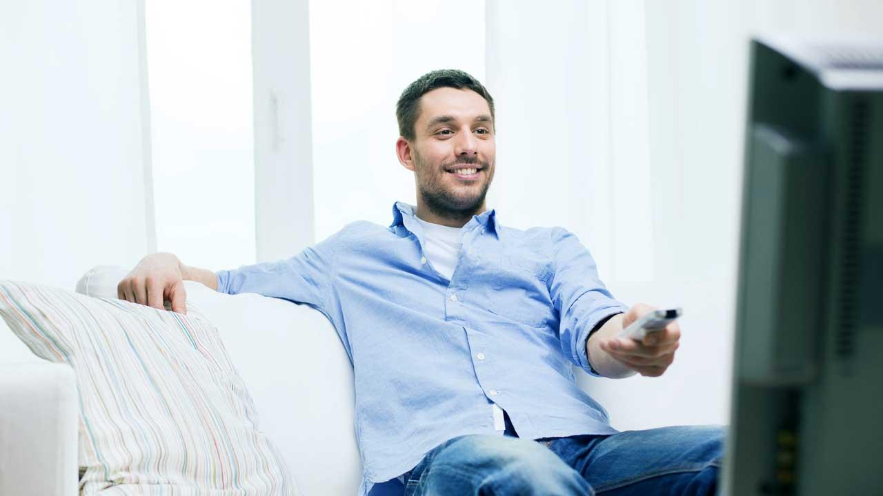 Mann schaut zufrieden Fernsehen