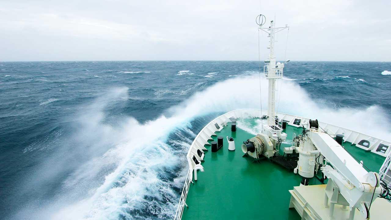 Schiff im Meer, Wasser spritzt beim Bug hoch